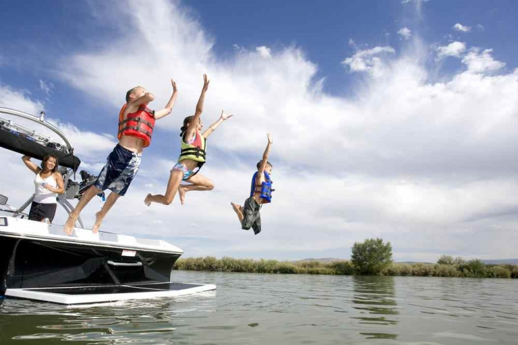 Kids jumping from boat into lake